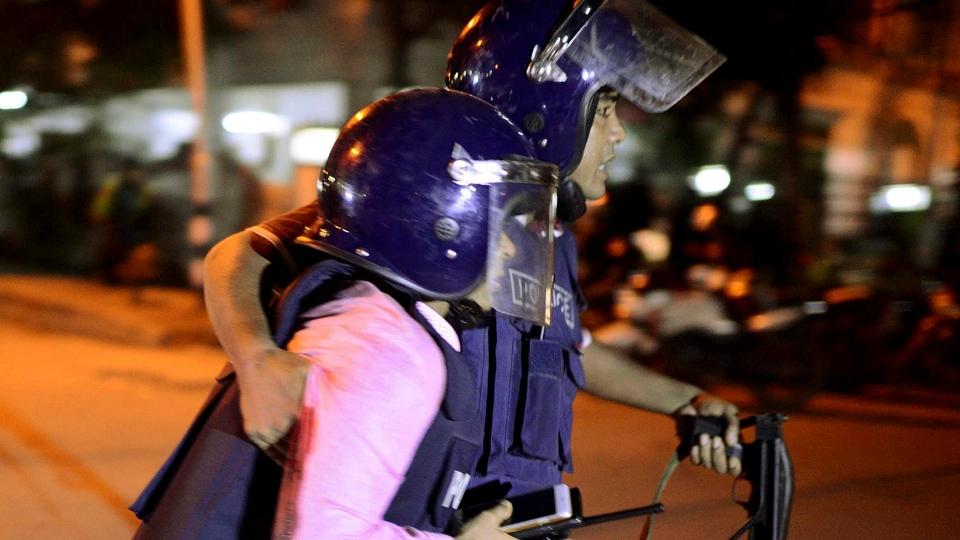An unidentified security personnel is taken for medical attention after a group of gunmen attacked a restaurant popular with foreigners in a diplomatic zone of the Bangladeshi capital Dhaka, Bangladesh, Friday, July 1, 2016.  (AP Photo)