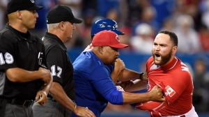 Toronto Blue Jays' catcher Russell Martin is held back by coaching staff as he reacts fiercely to home plate umpire Vic Carapazza's decision to eject him during thirteenth inning MLB baseball action against the Cleveland Indians, in Toronto on Friday, July 1, 2016. Martin's was Carapazza's third ejection of the game. (THE CANADIAN PRESS/Frank Gunn)