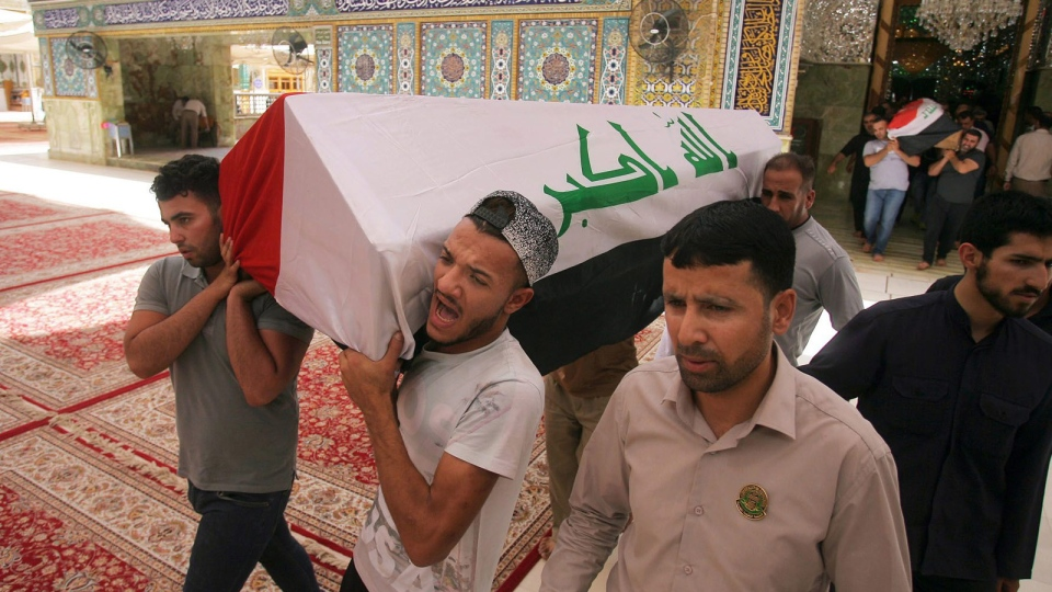 Mourners carry the Iraqi flag-draped coffins of bomb victims, Talib Hassan, 35, and Hamza Jabbar, 37, during their funeral procession at the holy shrine of Imam Ali in Najaf, 100 miles (160 kilometers) south of Baghdad, Iraq, Sunday, July 3, 2016. (AP Photo/Anmar Khalil)