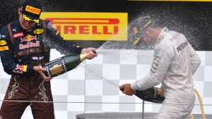 Mercedes driver Lewis Hamilton, of Britain, is sprayed with champagne by Red Bull driver Max Verstappen after the Formula One Grand Prix, at the Red Bull Ring in racetrack, in Spielberg, Austria, Sunday, July. 3, 2016. (AP Photo/Kerstin Joensson)