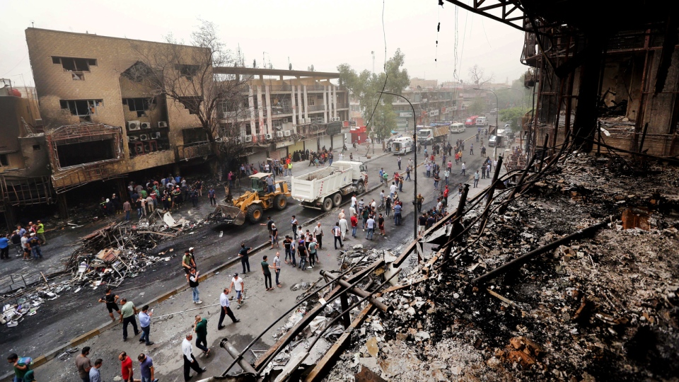 Iraqi security forces and civilians gather at the site after a car bomb hit Karada, a busy shopping district in the center of Baghdad, Iraq, Sunday, July 3, 2016. (AP Photo/Hadi Mizban)
