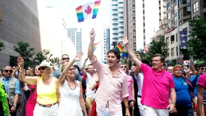 Ontario Premier Kathleen Wynne, left to right, Prime Minister Justin Trudeau and Toronto Mayor John Tory wave to spectators at the annual Pride Parade in Toronto on Sunday, July 3, 2016 (Nathan Denette / THE CANADIAN PRESS)