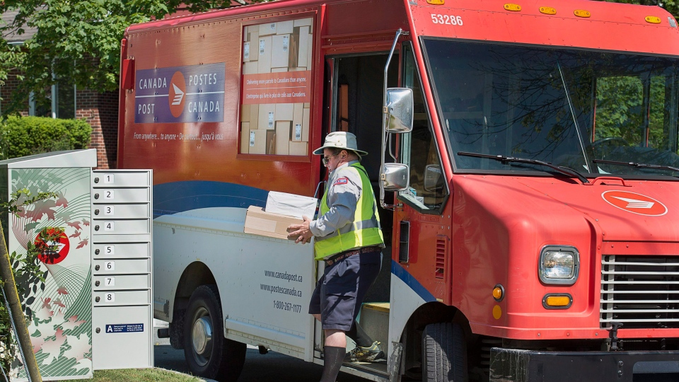 A Canada Post employee fills a community mail box in Dartmouth, N.S. on Thursday, June 30, 2016. (THE CANADIAN PRESS/Andrew Vaughan)