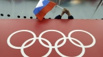 A Russian skating fan holds the country's national flag over the Olympic rings before the start of the men's 10,000-meter speedskating race at Adler Arena Skating Center during the 2014 Winter Olympics in Sochi, Russia on Feb. 18, 2014. (AP Photo/David J. Phillip, file)