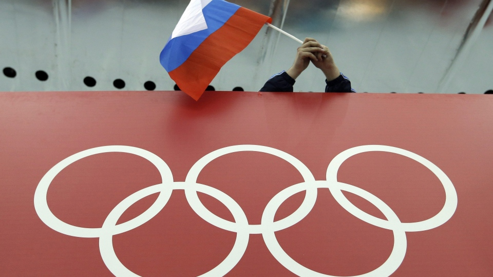 A Russian skating fan holds the country's national flag over the Olympic rings before the start of the men's 10,000-metre speedskating race at Adler Arena Skating Center during the 2014 Winter Olympics in Sochi, Russia on Feb. 18, 2014. (AP Photo/David J. Phillip)