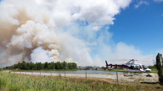 A blaze broke out in the popular Burns Bog conservation area in Delta on Sunday morning, spreading across dozens of hectares and sending huge plumes of smoke over Metro Vancouver. July 3, 2016. (CTV/Chopper 9/Pete Cline)