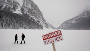 Tourists walk on the ice in Lake Louise, Alta., Thursday, Jan. 21, 2016. (THE CANADIAN PRESS/Jeff McIntosh)