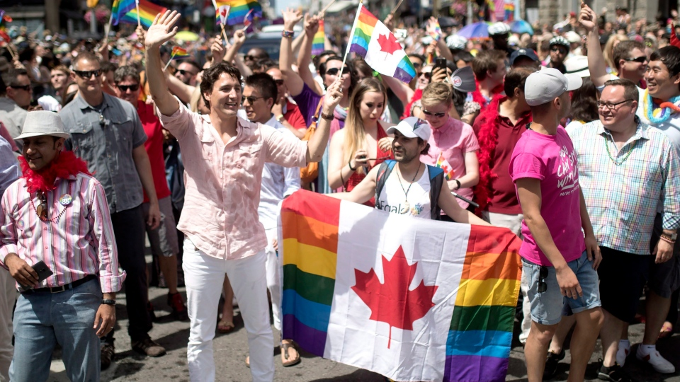 Prime Minister Justin Trudeau marches alongside Bassel Mcleash in the annual Pride Parade, in Toronto, on Sunday, July 3, 2016. (THE CANADIAN PRESS/Mark Blinch)