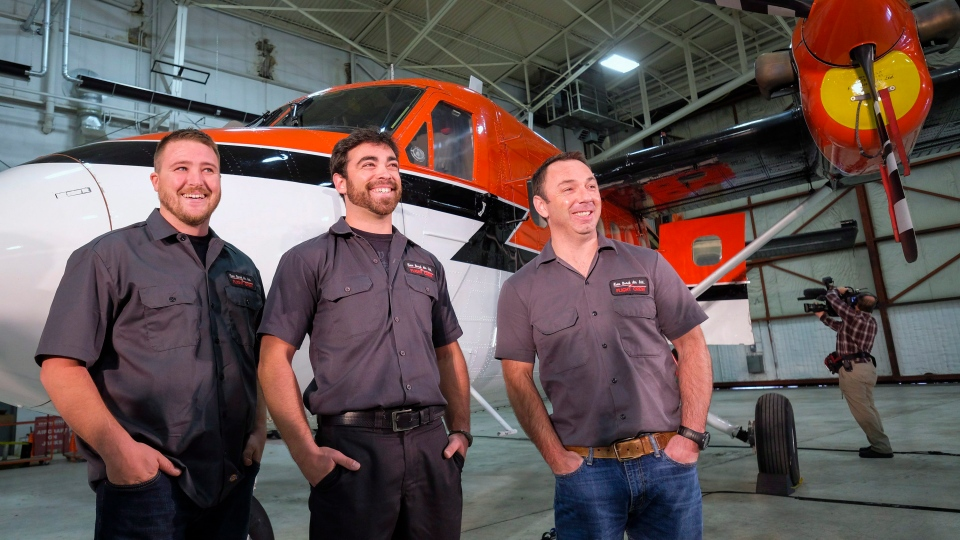 Kenn Borek Air crew members pose with the Twin Otter airplane they used in a successful medical evacuation of two researchers from Antarctica, in Calgary, Alta., Tuesday, July 5, 2016. (Jeff McIntosh / THE CANADIAN PRESS)