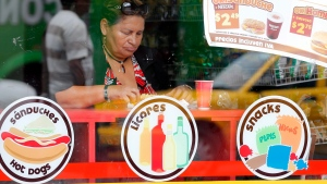 A woman stops for lunch at a fast food restaurant in Quito, Ecuador, on Wednesday, Sept. 3, 2014. (AP Photo/Dolores Ochoa)