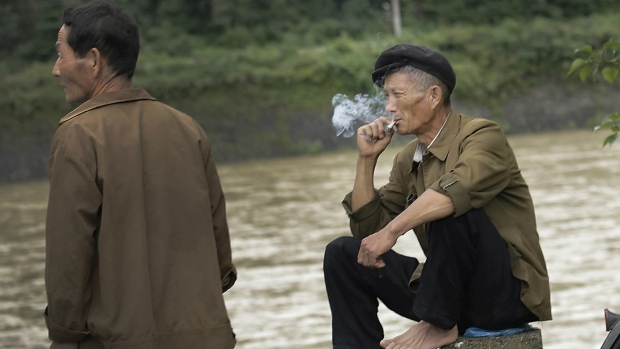 North Korean men sit and smoke by a river in the North Pyongan Province, North Korea on July 26, 2014. (AP / Wong Maye-E)