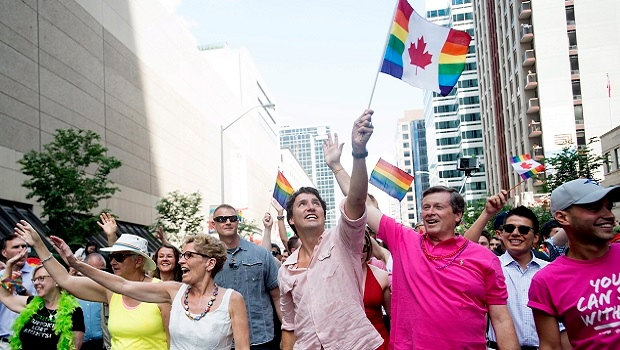 Ontario Premier Kathleen Wynne, left to right, Prime Minister Justin Trudeau and Toronto Mayor John Tory wave to spectators at the annual Pride Parade in Toronto on Sunday, July 3, 2016. (THE CANADIAN PRESS/Nathan Denette)