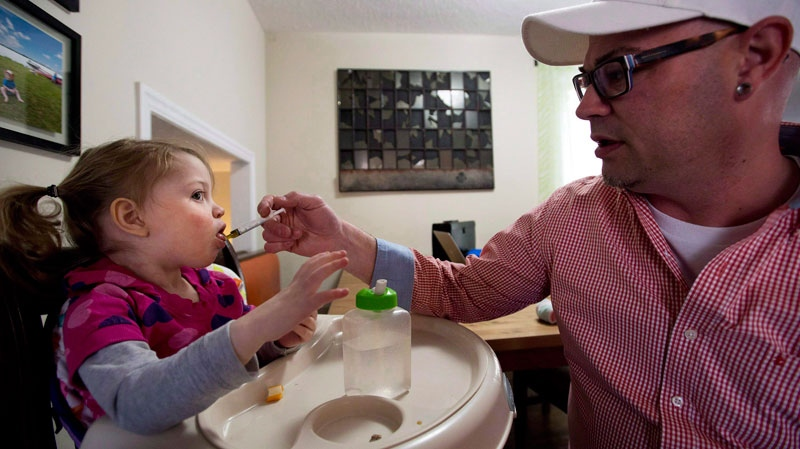 Alex Repetski, right, gives his two-year-old daughter Gwenevere oil-based medical marijuana to help control her seizures in Toronto on April 7, 2015. (THE CANADIAN PRESS/Nathan Denette)