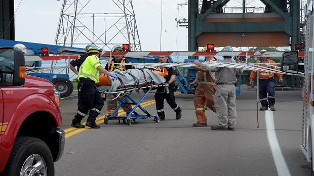 An injured construction worker is taken to an ambulance after an incident in Burlington on July 6, 2016.
