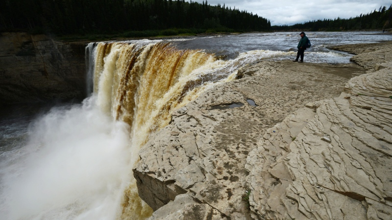 A man stands at the edge of Alexandra Falls on the Hay River south of Hay River, Northwest Territories on Tuesday, August 20, 2013. (Sean Kilpatrick / THE CANADIAN PRESS)