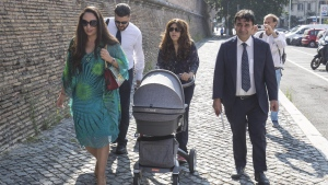 Public relations expert Francesca Chaouqui, center, arrives, with her newly born son Pietro, and her husband Corrado Lanino, second from left, at the Vatican for her trial, Tuesday, July 5, 2016. (Giuseppe Lami/ANSA via AP Photo)