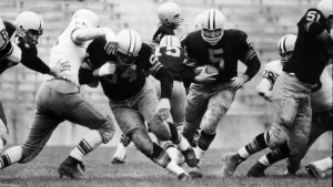 In this Aug. 10, 1959 file photo, Paul Hornung (5) of the Green Bay Packers goes through the line in an inter-squad game in Green Bay, Wis. Pro football Hall of Famer and former Heisman Trophy winner Hornung on Thursday, July 7, 2016, sued equipment manufacturer Riddell Inc., saying their football helmets that he wore during his professional career in the 1950s and '60s failed to protect him from brain injury. (AP Photo, File)