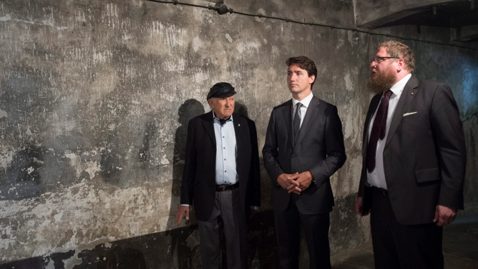 Canadian Prime Minister Justin Trudeau and Auschwitz survivor Nate Leipciger (left) listen to Director of the Auschwitz-Birkenau State Museum Dr. Piotr Cywinski as he speaks about the gas chamber they are standing in during a tour of the Auschwitz-Birkenau State Museum in Auschwitz, Poland Sunday July 10, 2016. (Adrian Wyld / THE CANADIAN PRESS)