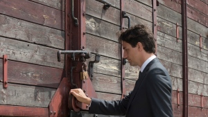 Canadian Prime Minister Justin Trudeau touches a rail car during a tour of the Auschwitz-Birkenau State Museum in Auschwitz, Poland Sunday July 10, 2016. (Adrian Wyld / THE CANADIAN PRESS)