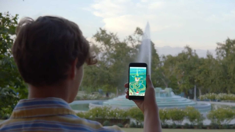 A boy plays Pokemon GO in a still image from a promotional video. (@Pokemon /Twitter)
