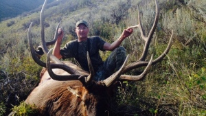 This undated photo provided by the Colorado Parks and Wildlife shows Thad Bingham with a bull elk in Colorado. (Colorado Parks and Wildlife via AP)