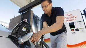In this photo taken Thursday, Sept. 17, 2015, Darshan Brahmbhatt, plugs a charger into his electric vehicle at the Sacramento Municipal Utility District charging station in Sacramento, Calif. (AP Photo/Rich Pedroncelli)