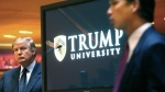 Donald Trump, left, listens as he's introduced at a news conference in New York where he announced the establishment of Trump University in this May 23, 2005 file photo. (File/The Associated Press)