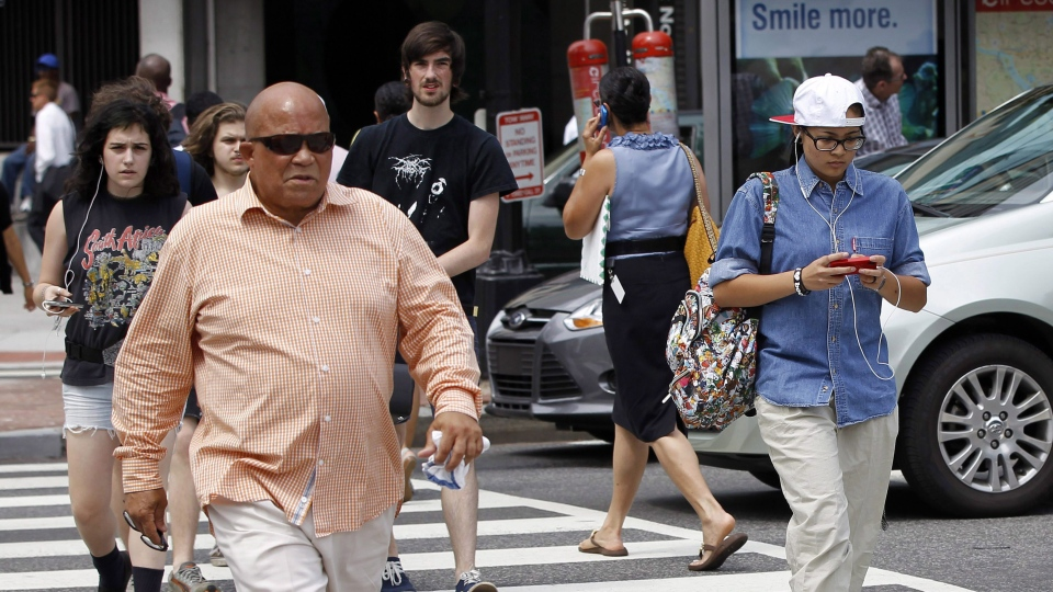 A pedestrian texts while crossing the street in this July 2012 file photo. (AP / Pablo Martinez Monsivais)
