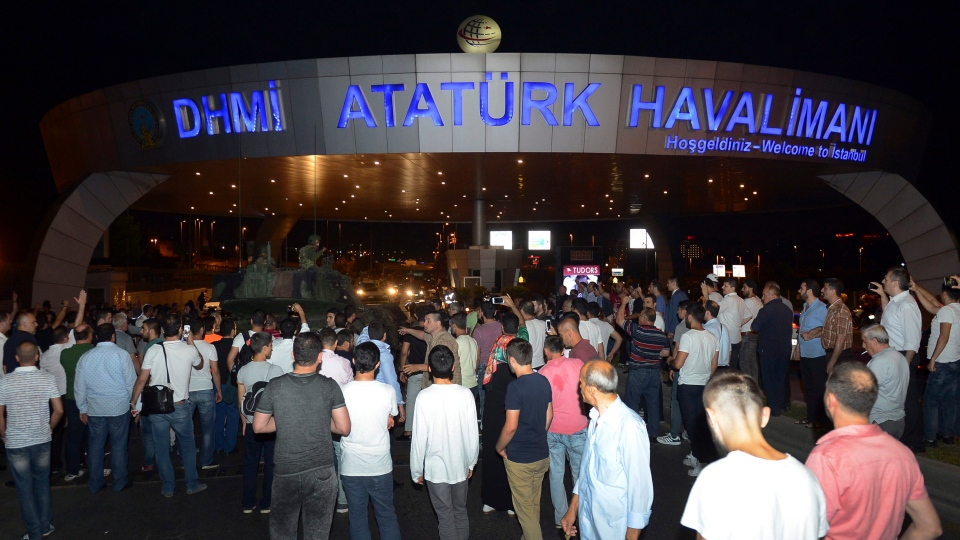 People stand in front of a tank parked in the entrance to Istanbul's Ataturk airport, early Saturday, July 16, 2016. (Ismail Coskun / IHA via AP)
