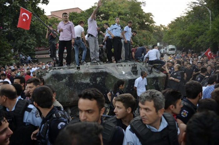 People gather and some stand atop of a Turkish army, armoured vehicle in Ankara, early Saturday, July 16, 2016. (AP)