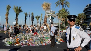 A police officer surveys people gathering around a floral tribute for the victims killed during a deadly attack, on the famed Boulevard des Anglais in Nice, southern France, Sunday, July 17, 2016. (AP / Laurent Cipriani)