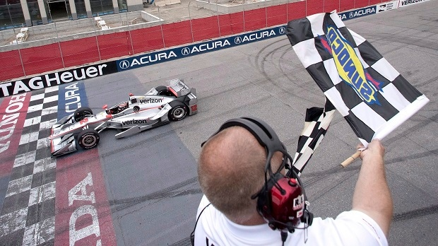 Will Power, of Australia, takes the checkered flag as he crosses the finish line to win the Honda Indy Toronto in Toronto on Sunday, July 17, 2016. (THE CANADIAN PRESS/Mark Blinch)