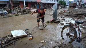 In this Sunday, July, 10, 2016 photo released by Xinhua News Agency, a woman clears mud and debris on a street following Typhoon Nepartak hit in Minqing county in southeast China's Fujian province. (Zhang Guojun/Xinhua via AP)