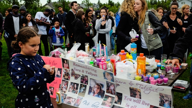 Mourners gather at a vigil for Calgary homicide victims Sara Baillie and her five-year-old daughter Taliyah Marsman, in Calgary, on Sunday, July 17, 2016. (Jeff McIntosh / THE CANADIAN PRESS)