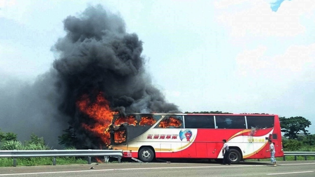 In this photo provided by Yan Cheng, a policeman and another man try to break the windows of a burning tour bus on the side of a highway in Taoyuan, Taiwan, Tuesday, July 19, 2016. (Yan Cheng/Scoop Commune via AP)