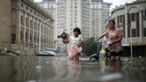 A child carries kettles through a flooded street with a woman in Tianjin, China on Wednesday, July 20, 2016. (Chinatopix)