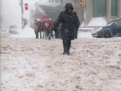A woman tries to cross a Toronto intersection as snow piles up the on streets on Wednesday, Jan. 28, 2009.
