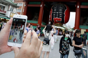 A man tries to catch a Pikachu, a Pokemon character, while he plays 'Pokemon Go' in front of Kaminarimon, or Thunder Gate, at the Sensoji temple in Tokyo's Asakusa shopping and tourist district, Friday, July 22, 2016. (AP Photo/Eugene Hoshiko)
