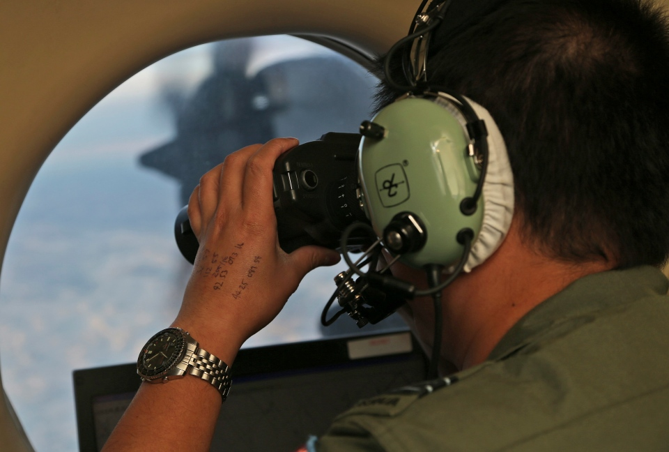 Flight Officer Jack Chen uses binoculars at an observers window on a Royal Australian Air Force P-3 Orion during the search for missing Malaysia Airlines Flight MH370 in Southern Indian Ocean, Australia on March 22, 2014. (AP / Rob Griffith)