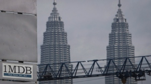 In this Wednesday, July 8, 2015 photo, a 1MDB (1 Malaysia Development Berhad) logo is set against the Petronas Twin Towers at the flagship development site. (AP Photo / Joshua Paul)