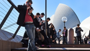 Dozens of people gather to play Pokemon Go in front of the Sydney Opera House on July 15, 2016. (AFP PHOTO/William West)