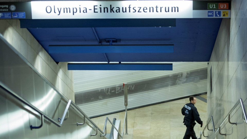 A policeman checks a closed metro station near the the scene of a shooting in Munich, Germany on Saturday, July 23, 2016. (AP / Jens Meyer)