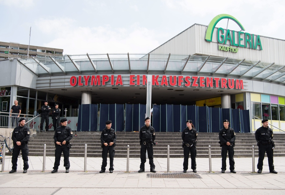 Police stand in front of the Olympic shopping center where a shooting took place leaving nine people dead the day before on Saturday, July 23, 2016 in Munich, Germany. (AP / Sebastian Widmann)