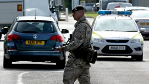 An armed guard patrols, at RAF Marham in Norfolk, after a serviceman was threatened with a knife near to the base, in Marham, England, Thursday July 21, 2016. (Chris Radburn/PA via AP)