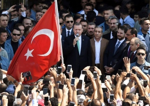 In this Friday, July 22, 2016 photo, Turkey's President Recep Tayyip Erdogan, centre, surrounded by his entourage and security detail, talks to people gathered after Friday prayers at a mosque, in Ankara, Turkey. (Press Presidency Press Service via AP)