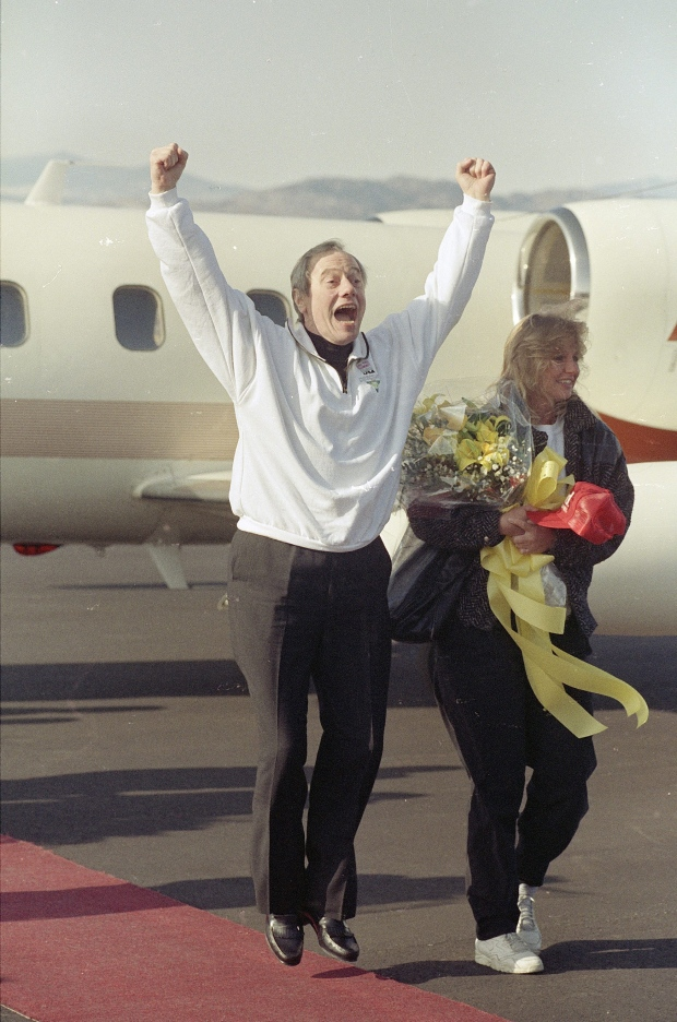In this Dec. 1, 1991 file photo, Thomas Sutherland jumps and shouts after arriving at Fort Collins-Loveland Airport outside his hometown of Fort Collins, Colo. (AP / Jeff Robbins)