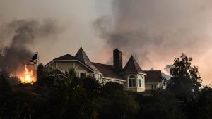 A wildfire burns close to a home near Sand Caynon and Placerita Caynon in Santa Clarita, Calif., Saturday, July 23, 2016. (AP / Ryan Babroff)