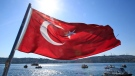 FILE - A Turkish flag flies near the Bosporus strait prior to the Bosporus Cross-Continental Swimming Race in Istanbul, Turkey, Sunday, July 24, 2016. (AP / Lefteris Pitarakis)