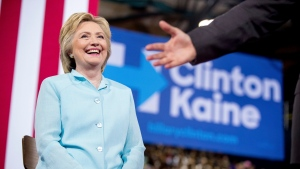 Sen. Tim Kaine, D-Va., right, accompanied by Democratic presidential candidate Hillary Clinton, left, speaks at a rally at Florida International University Panther Arena in Miami, Saturday, July 23, 2016. (AP Photo/Andrew Harnik)