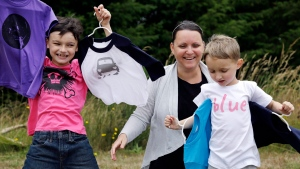 In this Thursday, July 7, 2016, photo, Martine Zoer poses for a photo with her sons Tyler, 8, left, and Tristan, 5, as they wear and display some of the gender-neutral clothing she creates, in Mill Creek, Wash. (AP / Elaine Thompson)